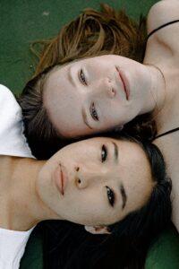 women lying on green surface