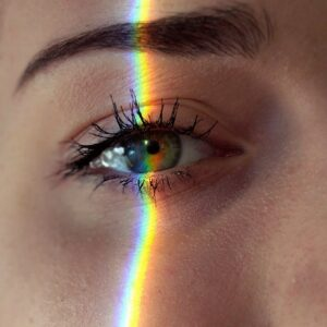 anonymous woman with rainbow light on face